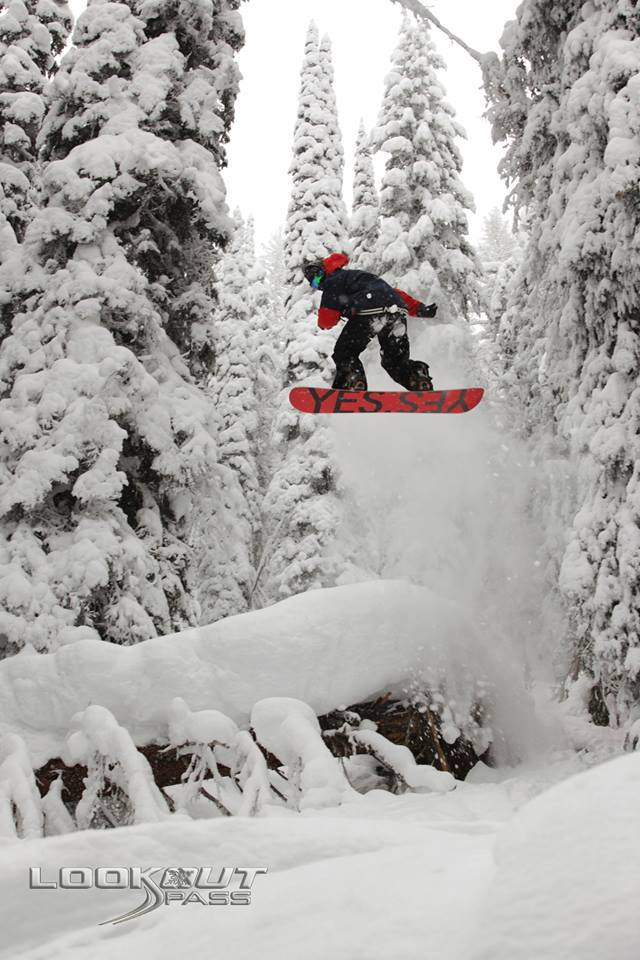 Snowboarder soaring over jumps in the middle of the forest