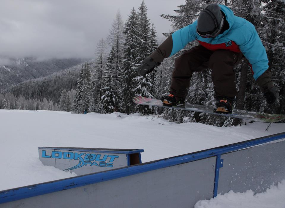 Snowboarder soaring over jump for guests to see, near the deck